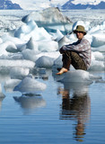 Man, sitting on ice in Jokulsarlon lagoon, Iceland
