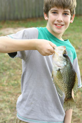 young boy holding fish he caught