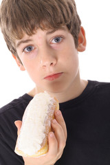 boy with worried look eating a donut