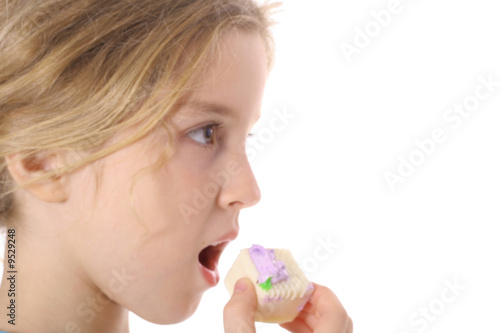 little girl eating a petit four