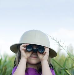Young child looking through toy binoculars wearing safari hat