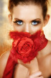 Blond beautiful woman with red silk flowers and feathers