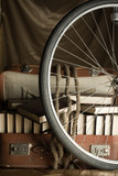 Bicycle wheel and Old torn suit-case full of books with rope