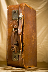 Old and worn Suit-Case on gold background