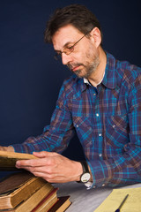 Professor at work, working with very old books and taking notes