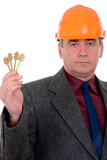 middleaged constructor holding a key poster