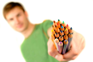guy suggests and holds  set of color pencils in  hand