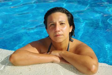 Mujer descansando en el bordillo de la piscina