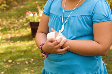 Young girl holding her sore wrist with a sloppy bandage on it