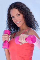 Young pretty woman doing fitness exercise with two weight