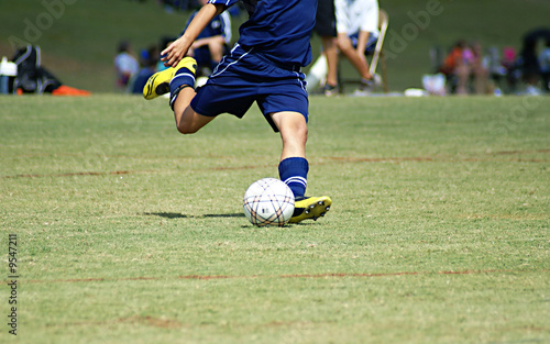 Young boy strking a soccer ball in a game.