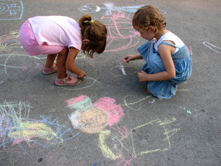 two little girls drawing on the street