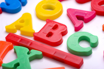Brightly colored plastic alphabet letters on a white background