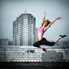 girl jumping on the roof against city