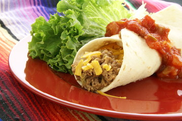 Mexican burrito with beef beans cheese and salsa on red plate