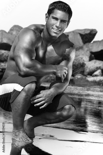 young man in bathing suit with feet in the water