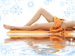 long legs of relaxed lady with orange towel on white sand