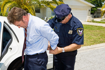 Businessman being handcuffed and placed under arrest