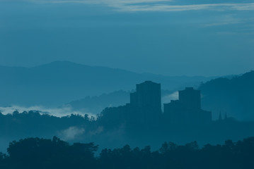 Misty morning of high rise buildings on hilly residential area.