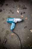 A backyard mechanics impact wrench laying on the blacktop. poster