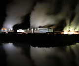 Geothermal powerplant at night in winter, steam time blurred poster