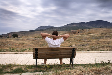 Man sits on bench looking at ancient city Hierapolis, Turkey