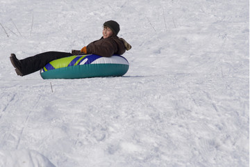 Boy sliding downhill on tube