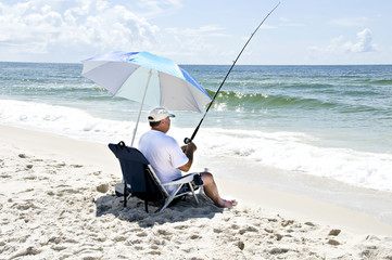 A man sitting in a beach chair fishing