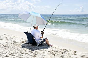 A man sitting in a beach chair fishing