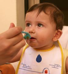 bambino mangia con cucchiaino