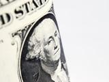 US dollars focused on President Washington over white poster