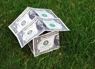 House shape made from US dollars on grass
