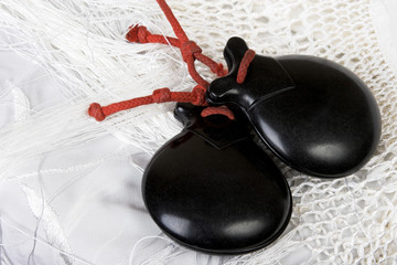 Black spanish castanets on a white shawl