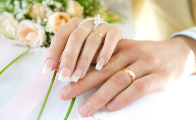 Ring & hands over white and flowers, wedding day