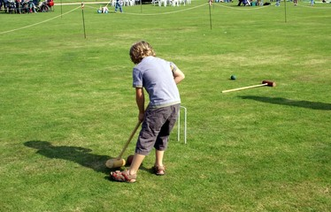 boy playing croquet