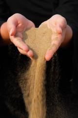 sand running through hands as a sym