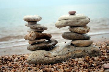 double balanced pyramids against each other on sea shore