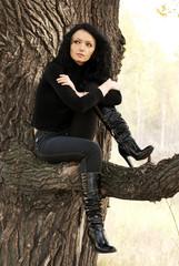 beautiful melancholic woman sitting on the tree