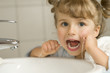 Cute girl cleaning teeth by floss in bathroom - 9604451