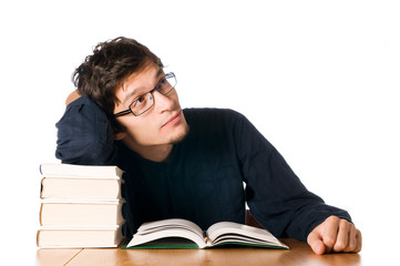 Pensive young man studying on a stack of books