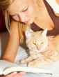 Young beautiful woman with a cat reading a book