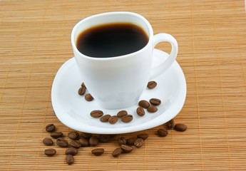 White cup of coffee with coffee grains