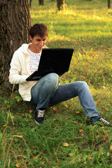 Student sitting by tree works with laptop