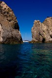 Yacht cruising between two rocks in Ponza island, Italy