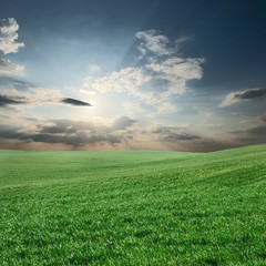Green field with sunlight beams shining through the clouds