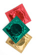 Coloured condoms in their wrappers on a white background