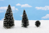 Three evergreen trees on snow with snowflake background poster