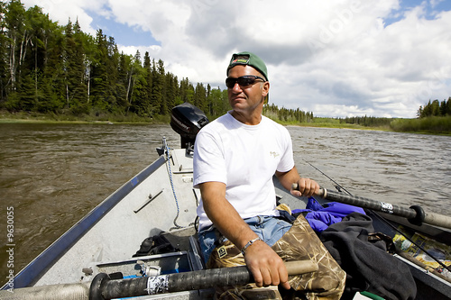 Man Rowing a Drift boat on the river