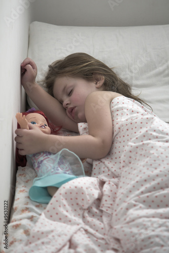 The little girl strong sleeps, embracing a doll