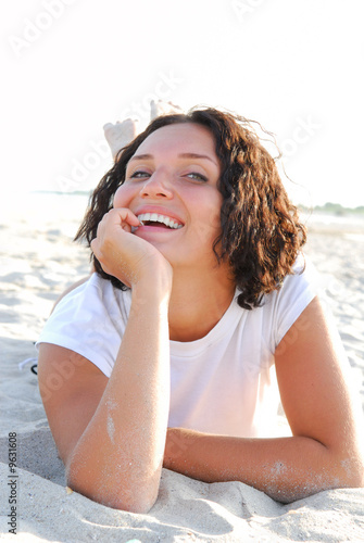 Portrait of beautiful young woman lying on beach smiling.